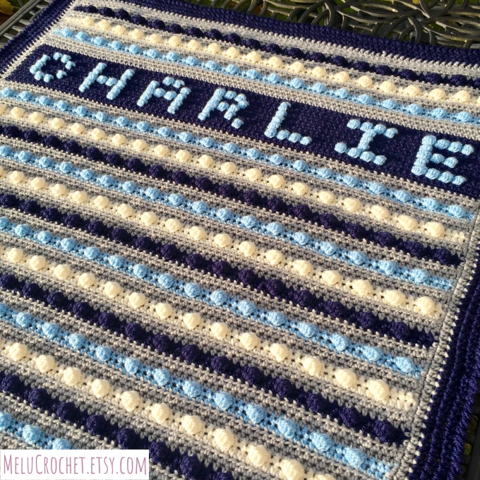 Personalised crochet blanket for 'Charlie' with alternating colours blue, grey, cream, navy blue.