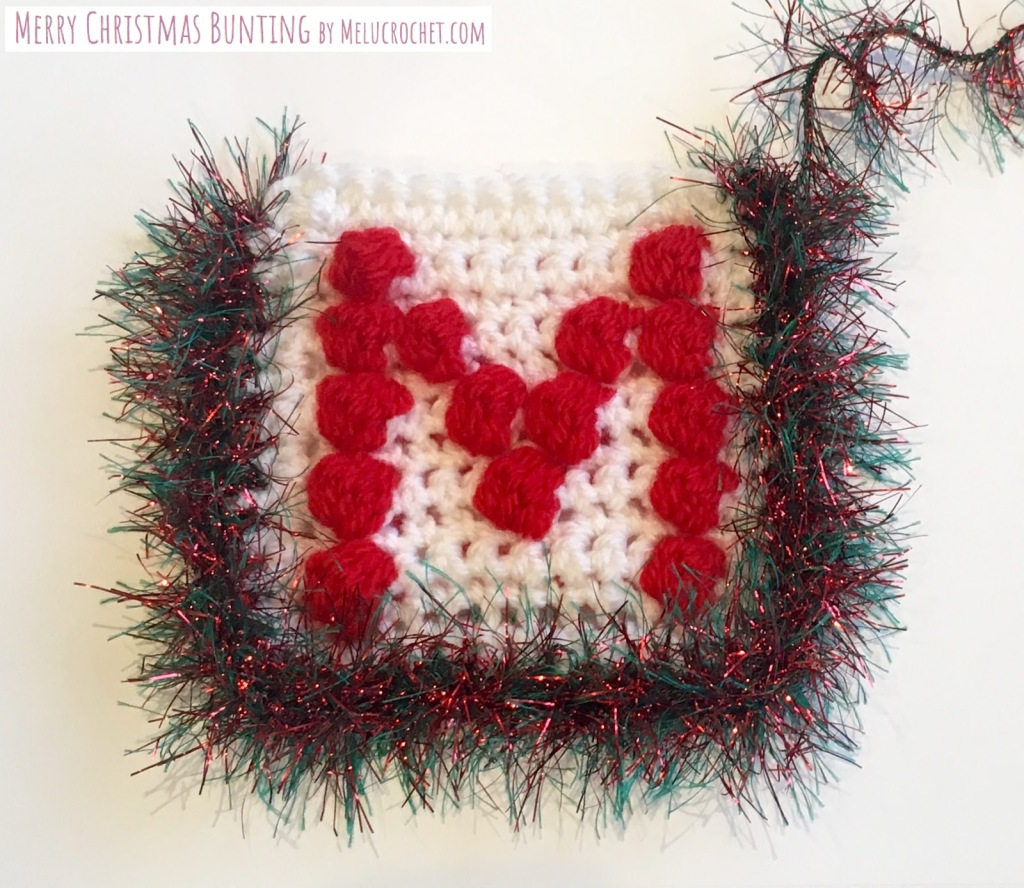crochet bobble stitch square with white yarn and a red letter M, with tinsel yarn crocheted around the edge