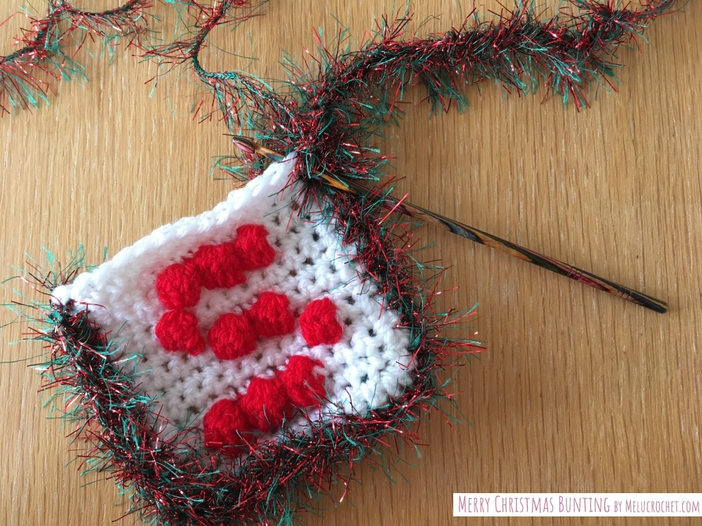 crochet bobble stitch square with white yarn and a red letter S, with christmas tinsel yarn crocheted around the edge and crochet hook inserted into yarn