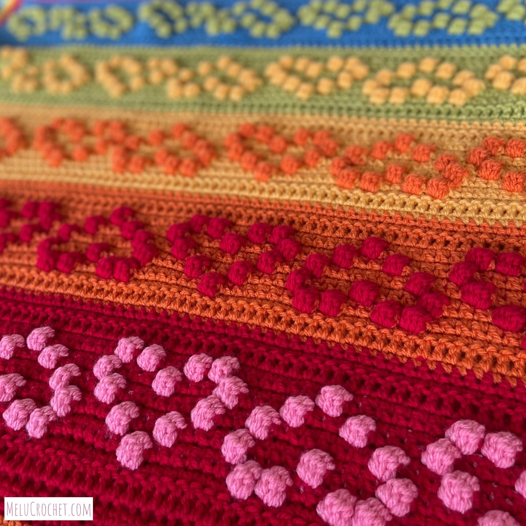 Rainbow coloured blanket with raised bumps that are formed using the crochet bobble stitch in the shape of hearts fading out of focus in the distance