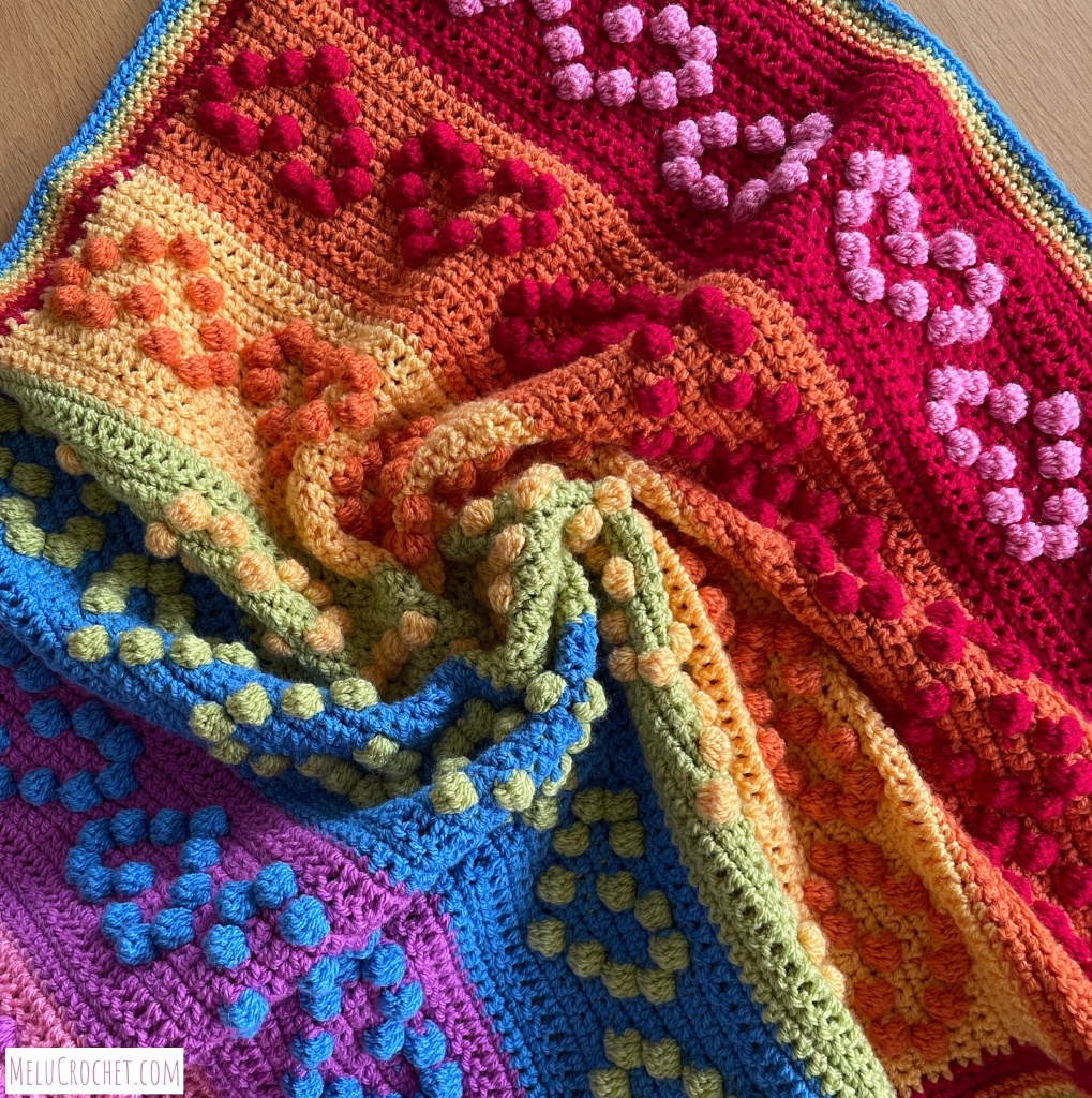 Rainbow coloured blanket with raised bumps that are formed using the crochet bobble stitch in the shape of hearts. The blanket has been swirled.