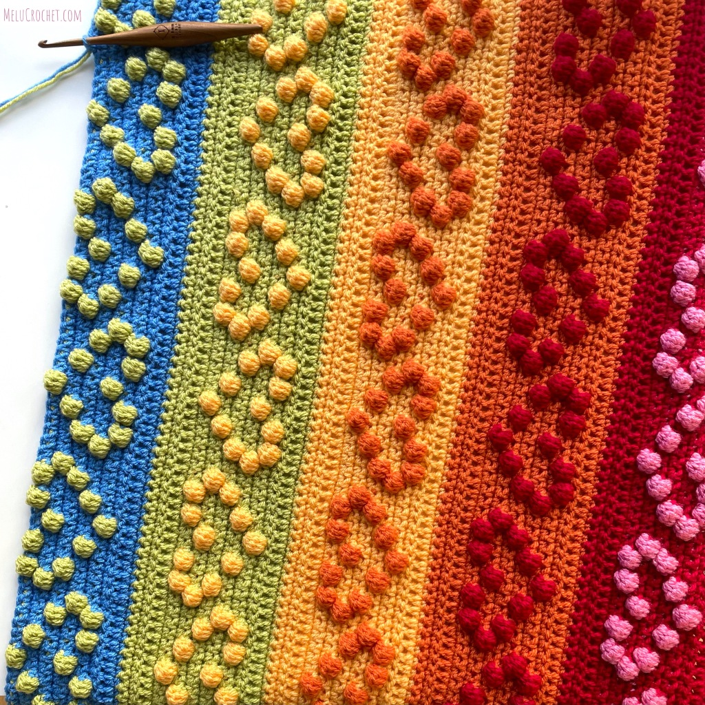 Progress photo of Rainbow coloured blanket with raised bumps that are formed using the crochet bobble stitch in the shape of hearts, with furls crochet hook