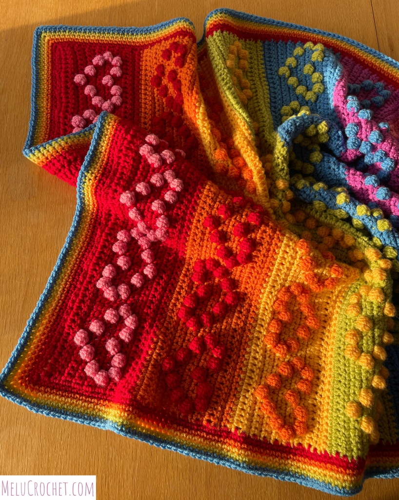 Rainbow coloured blanket with raised bumps that are formed using the crochet bobble stitch in the shape of hearts, crumpled up and in sunshine