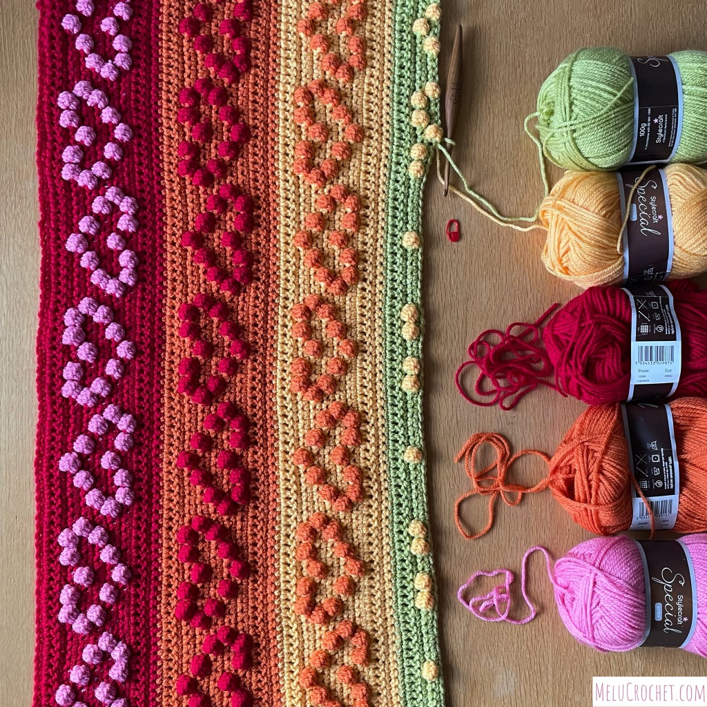 Construction of a Rainbow coloured blanket with raised bumps that are formed using the crochet bobble stitch in the shape of hearts, each colour has a ball of stylecraft wool that is being used, along with a furls crochet hook